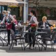 Waitresses with a mask and gloves disinfecting the table of an outdoor bar, café or restaurant